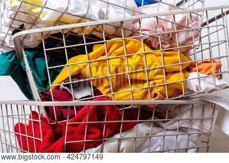 Colorful Clothes In Baskets In Laundry Room. Improper Storage Of Things, Mess, Disorder. Getting Rid
