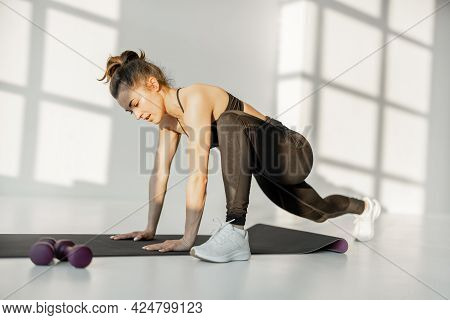 Beautiful Athletic Woman Doing Lunges And Squats During A Fitness Training At White Sunny Room Alone