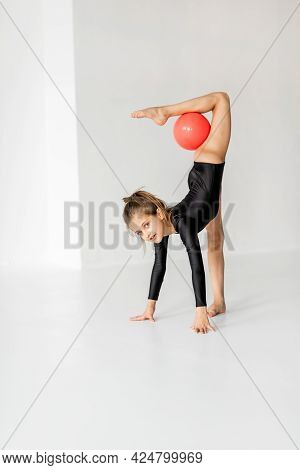 Little Girl Practising Rhythmic Gymnastic With A Ball At White Room. Childrens Gymnastics And Traini