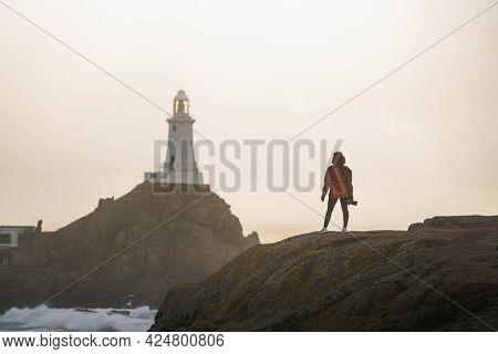 Female traveler at La Corbiere Lighthouse on Isle of Jersey, Scotland