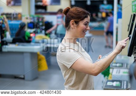 Caucasian Woman Uses A Self-checkout Counter. Self-purchase Of Groceries In The Supermarket Without