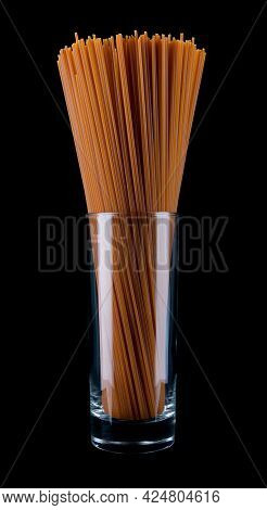 Long Spaghetti Isolated On A Black Background. Tomato Pasta In A Glass Glass. Colored Spaghetti.