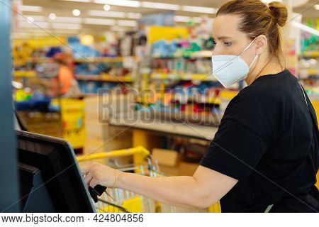 Woman In A Supermarket At A Self-checkout Counter Shopping In A Medical Mask, Covid Security, City L