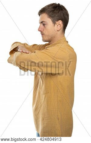 Young Handsome Tall Slim White Man With Brown Hair With Crossed Arms Standing Sideways In Ochre Shir
