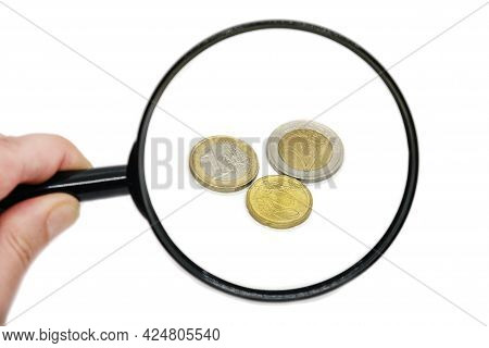 Euro Coins Magnified In A Hand-held Magnifier On A White Background. A Man Holds A Magnifying Glass