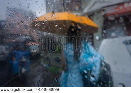 Image Shot Through Raindrops Falling On Wet Glass, Abstract Blur Of Lady With An Yellow Unbrella - M