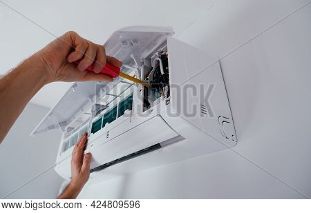 Repair And Maintenance Of The Air Conditioner. A Technician Repairs An Air Conditioner. Close-up Vie