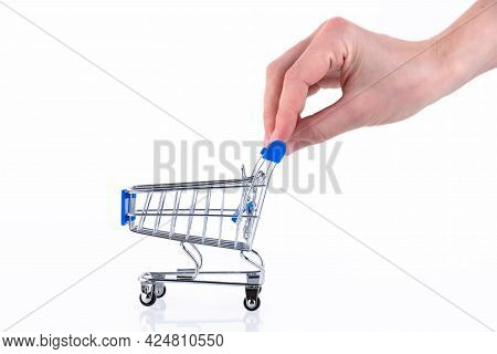 Female Hand With Fingers Pushing A Shopping Cart Isolated On White Background. Copy Space.