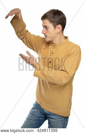 Young Handsome Tall Slim White Man With Brown Hair Doing Tai Chi Standing Sideways In Ochre Shirt In