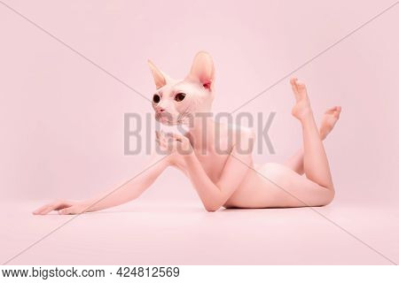 Young Naked Beautiful Girl Headed Of Sphynx Cat Head Posing Isolated On Pink Studio Background. Conc