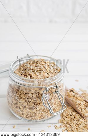 Raw Dry Oatmeal Flakes In A Glass Jar On A White Wooden Background. Healthy Food. Copy Space