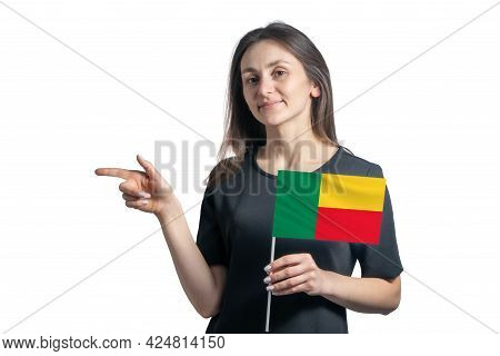 Happy Young White Woman Holding Flag Benin And Points To The Left Isolated On A White Background.