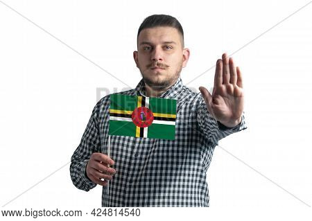 White Guy Holding A Flag Of Dominica And With A Serious Face Shows A Hand Stop Sign Isolated On A Wh