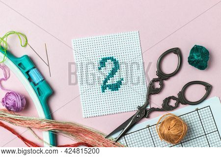 Green Number 2 Cross-stitch Embroidered Surrounded By Accessories For Embroidery: Threads Of Moulin