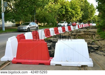 Red and white fences on the background of road works in the city. Construction fences on the road du