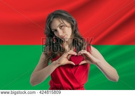 Love Burkina Faso. A Girl Holds A Heart On Her Chest In Her Hands Against The Background Of The Flag