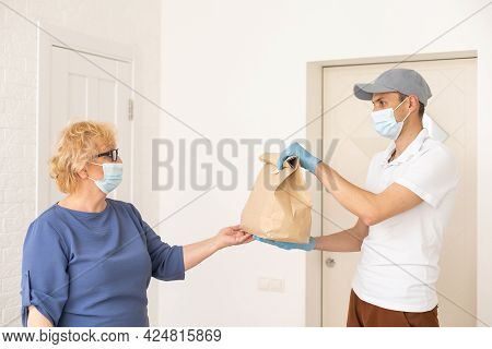 Young Male Volunteer In Mask Gives An Elderly Woman Boxes With Food Near Her House. Son Man Helps A