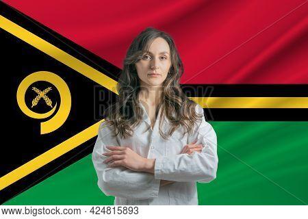 Medicine In Vanuatu. Happy Beautiful Female Doctor In Medical Coat Standing With Crossed Arms Agains