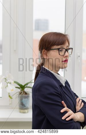 Young Strict Business Woman In A Blue Jacket And Glasses Is Thinking At The Window In The Office At