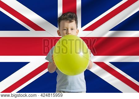 Children's Day In United Kingdom. White Boy With A Balloon On The Background Of The Flag Of United K