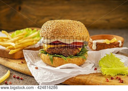 Ready-to-eat Delicious Hamburger And Hot French Fries. A Cutting Board Made Of Mango Wood In A Rusti