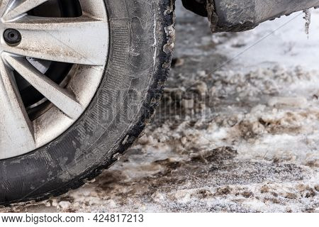 Close Up Photo Of Detail Of Car Back Wheel With Dirty Tire During Snowy Winter Day. Part Of Car Bump