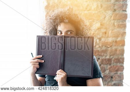 A Hairy Student Playfully Hides Behind A Book While Studying And Looks Away. Spies With Sly Eyes