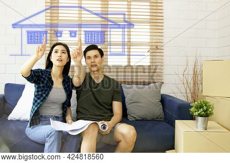 Happy Asian Couple Admires The Blueprints Of The Beautifully Designed Houses. There Is Excitement, S