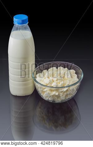 Cottage Cheese In The Transparent Glass Bowl, Plastic Bottle Of Milk On A Dark Reflective Surface