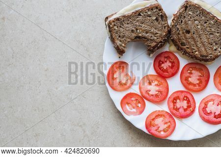 Toast Slices Of Bread Made From Spelled Flour Filled With Cheese With A Bite On It, Next To Sliced T