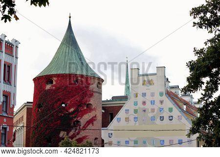 The Powder Tower (latvian: Pulvertornis) At Foggy Autumn Day.  The Powder Tower And Latvian Coat Of
