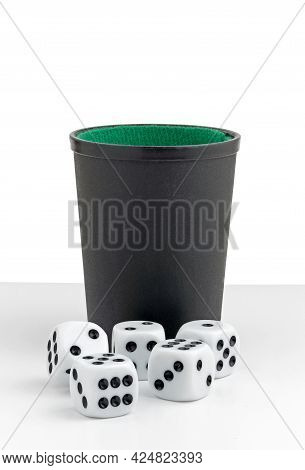 Five White Dice Lying In Front Of A Black Cup With Green Felt Lining On A White Background