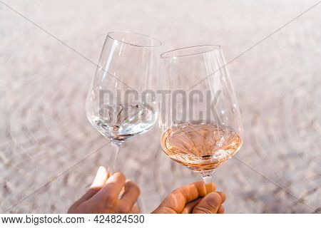 Two People Toasting Each Other Outdoors With Two Glasses Of Wine, Rose And White