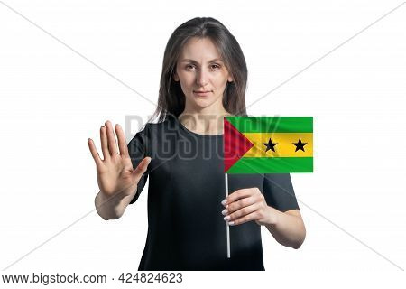 Happy Young White Woman Holding Flag Of Sao Tome And Principe And With A Serious Face Shows A Hand S