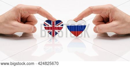 The Concept Of Friendship And Diplomatic Relations Between Russia And The Britain. Two Male Hands Ar