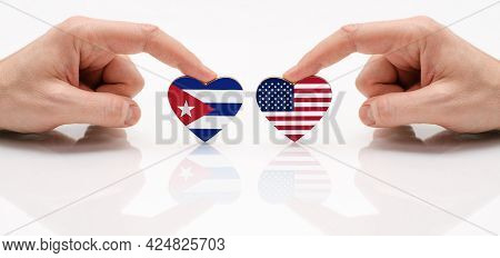 The Concept Of Friendship And Diplomatic Relations Between Cuba And Usa. Two Hands Are Holding Flags