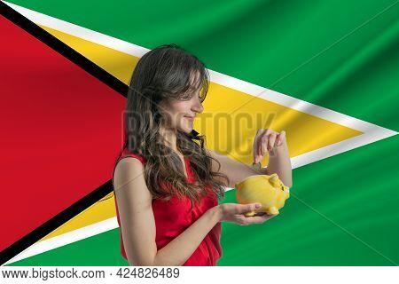 Economy In Guyana. Accumulating And Saving Money In Guyana. Woman Putting Money Coin In Piggy Bank F
