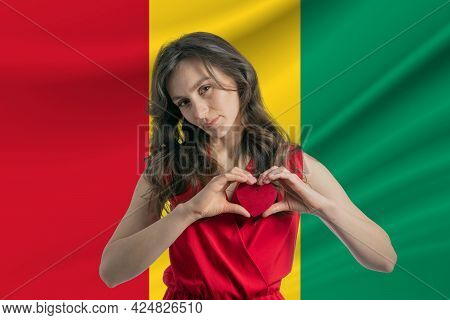 Love Guinea. A Girl Holds A Heart On Her Chest In Her Hands Against The Background Of The Flag Of Gu