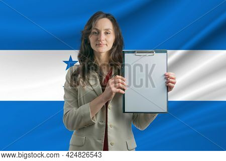Study In Honduras. Beautiful Woman Holding A Sheet Of Paper In Her Hands. Girl On The Background Of