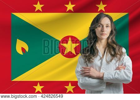 Medicine In Grenada. Happy Beautiful Female Doctor In Medical Coat Standing With Crossed Arms Agains