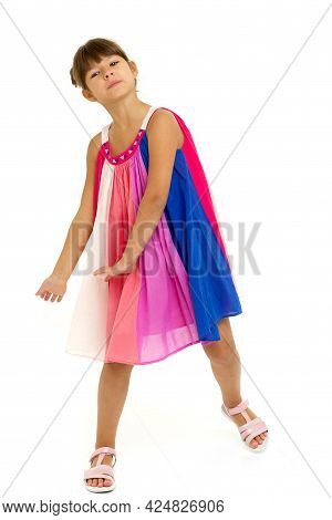 Girl With Outstretched Arms And Legs Wide Apart. Happy Girl In Bright Sundress Posing In Studio On I