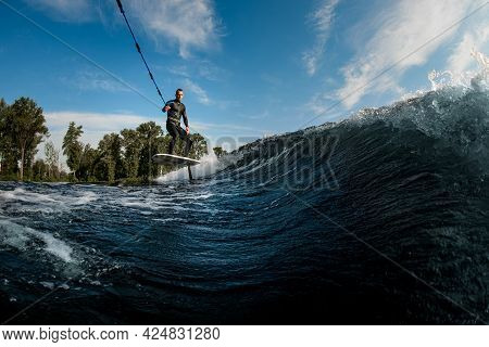 Young Athletic Man Vigorously Riding On The Wave With Foilboard
