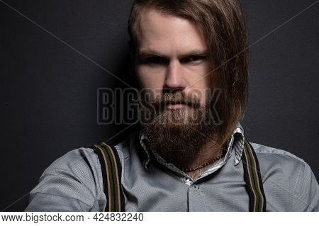 Portrait Of A Handsome Bearded Courageous Brutal Man In The Studio. He Looks Seductively Into The Ca