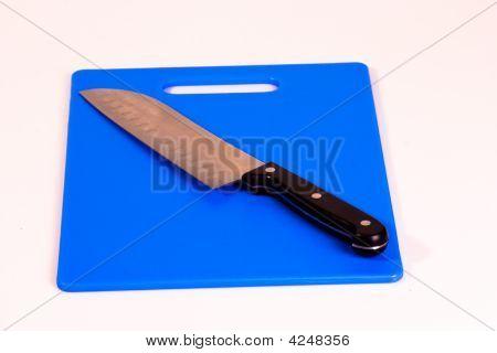 Santoku Knife On A Blue Cutting Board
