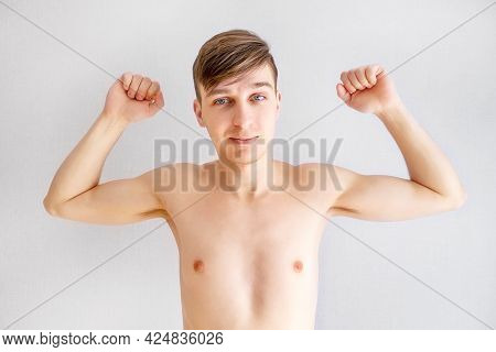 Handsome Young Man Muscle Flexing By The Wall In The Room