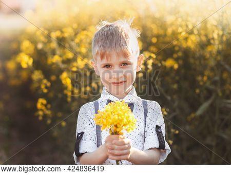 Little Cute Boy In An Oilseed Rape Field. Rural Landscape.