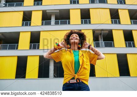 Happy Hipster Woman With Vitiligo Enjoying Life While Standing Against Background Of A Gray-yellow U