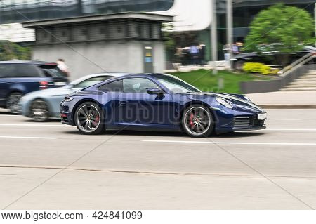 Moscow, Russia - May 2021: Porsche 911 Carrera 4s Rolling Shot Down The Street On High Speed. Blue S