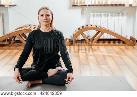 Young Woman Doing Yoga Exercises Sitting In Lotus Asana