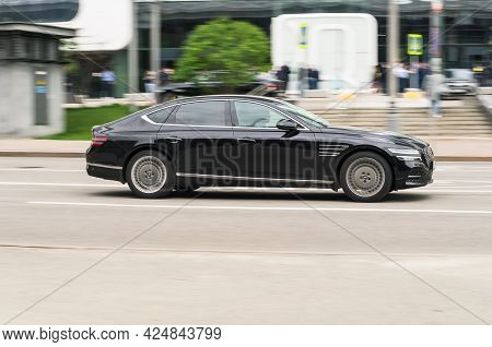 Moscow, Russia - May 2021: Side View Rolling Shot With Black Car In Motion. Genesis G80 Driving Alon